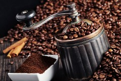 a coffee grinder and roasted coffee beans